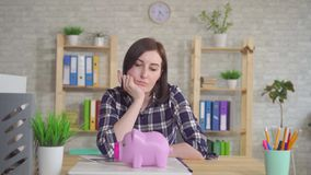 Young woman sitting at the table, puzzled, looks at the piggy bank. Young woman sitting at home at the table, puzzled, looks at the piggy bank stock video