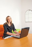 Young woman sitting at home using a laptop Stock Photo