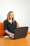 Young woman sitting at home using a laptop Royalty Free Stock Image