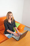 Young woman sitting at home using a laptop Royalty Free Stock Photos