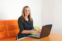 Young woman sitting at home using a laptop Stock Image