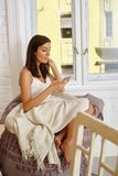 Young woman using mobile at home. Young woman sitting at home, using mobilephone, texting Stock Image