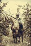 Young woman sitting on a horse Stock Photo