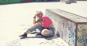 Young woman sitting in the hot sun waiting. At a skate park with her skateboard in front of a graffiti covered wall shielding her eyes with her hand stock video