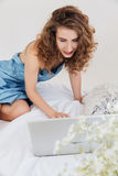 Young woman sitting indoors on bed using laptop computer. Photo of happy young woman sitting indoors on bed using laptop computer. Looking aside Stock Photography