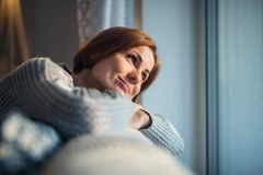 A young woman sitting indoors on a sofa at home, looking out of a window. A happy young woman sitting indoors on a sofa in the evening at home, looking out of a royalty free stock image