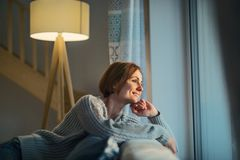 A young woman sitting indoors on a sofa at home, looking out of a window. A happy young woman sitting indoors on a sofa in the evening at home, looking out of a royalty free stock images