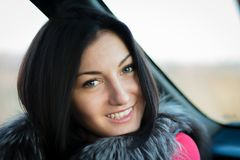 Young Woman Sitting Inside Car Smiling at Camera royalty free stock photo