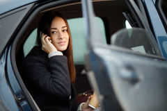 Young woman sitting inside car and talking on mobile phone Royalty Free Stock Images