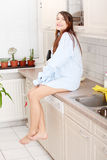 Young woman sitting on kitchen counter Royalty Free Stock Photography