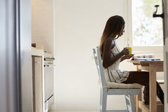 Young woman sitting in kitchen reading and drinking coffee Royalty Free Stock Image