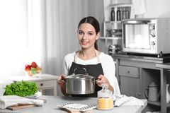 Young woman sitting at kitchen table. And holding saucepan Royalty Free Stock Photo