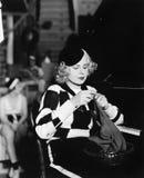 Young woman sitting and knitting at piano Stock Photo