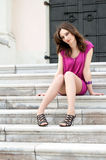 Young woman sitting on the ladder of old city Stock Photography