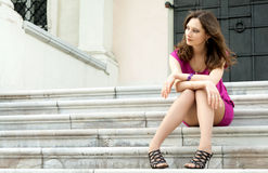 Young woman sitting on the ladder of old city Stock Images