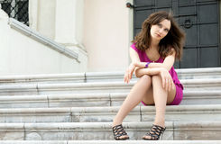 Young woman sitting on the ladder of old city Royalty Free Stock Photos