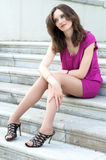 Young woman sitting on the ladder of old city Royalty Free Stock Images