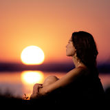 Young woman sitting on lake coast at sunset. Stock Image