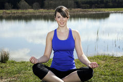 Young woman sitting by a lake in a lotus position Royalty Free Stock Photography