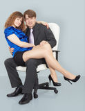Young woman sitting on lap of a man. Young woman sitting on the lap of a man sitting in a chair Royalty Free Stock Photography
