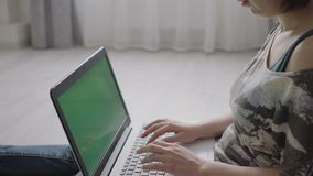 Young woman sitting at the laptop close-up. Young woman sitting on the floor at the laptop close-up stock footage