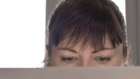 Young woman sitting on a laptop close-up near a window in the afternoon. Young woman sitting at the laptop close-up stock video footage