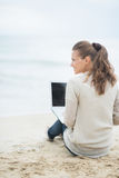Young woman sitting with laptop on cold beach. Young woman sitting with laptop on lonely cold beach Royalty Free Stock Images