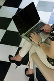 Young woman sitting with laptop Stock Photography