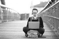 Young woman sitting with laptop on the pedestrian bridge. Black and white photography Royalty Free Stock Photography