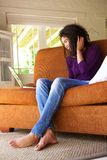 Young woman sitting with laptop on sofa Royalty Free Stock Photo