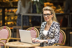 Young  woman sitting with laptop at street cafe. Royalty Free Stock Images