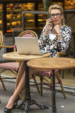 Young woman sitting with laptop in street coffee shops and talking on a cell phone. Royalty Free Stock Photo