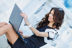 Young woman sitting with a laptop on a summer day Stock Image