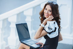 Young woman sitting with a laptop on a summer day. Beautiful business woman talking on mobile phone sitting on the stairs with laptop Royalty Free Stock Image