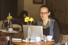 Young woman sitting with laptop at table in a cafe. Freelancer. Young woman sitting with laptop at table in a cafe Royalty Free Stock Photography