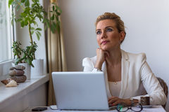 Young  woman sitting with laptop thoughtfully dreamy looks in the space. Royalty Free Stock Images