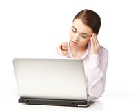 Young woman sitting at a laptop, on the white background. Lost in thought young woman sitting at a laptop, holding a hand on forehead, on the white background Stock Photography