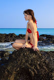 Young woman sitting on lava rocks. At a hawaii beach Royalty Free Stock Image