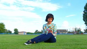 Young woman sitting on the lawn of the stadium uses a smartphone on a cloudy blue sky background. stock footage