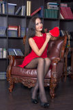 Young woman sitting in a leather chair and holding red heart Royalty Free Stock Image