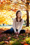 Young woman sitting in the leaves. Enjoying fall Stock Images