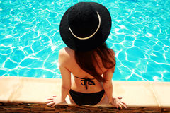 Young woman sitting on the ledge of the pool Stock Images