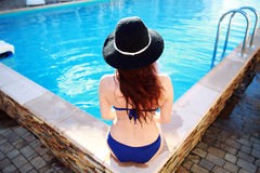 Young woman sitting on the ledge of the pool Royalty Free Stock Photo