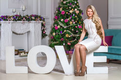 Young woman sitting on the letters. Young woman in evening dress sitting on the letters love in front of a Christmas tree Royalty Free Stock Images