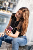 Young woman sitting  and listening to her  music Royalty Free Stock Images