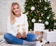 Young woman sitting in living room with decorated Christmas tree stock photo