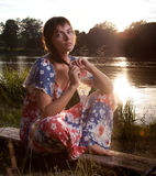 Young woman sitting on log stock photos