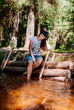 Young woman sitting on logs and lowered her feet into the river. Stock Image