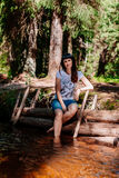 Young woman sitting on logs and lowered her feet into the river. Royalty Free Stock Photos