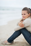 Young woman sitting on lonely beach looking into distance Stock Images